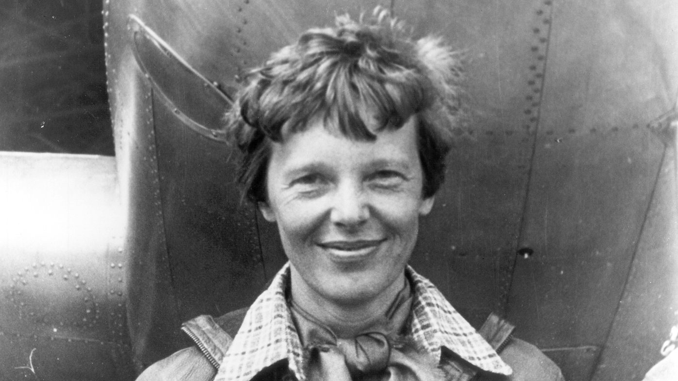 Amelia_Earhart_standing_under_nose_of_her_Lockheed_Model_10-E_Electra_small-e1571219171183